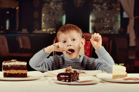 he is different: Little boy eating a slice of cake with gusto taking a big mouthful as he eyes the line up of different cakes on offer in front of him
