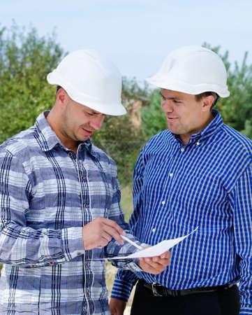 contrema�tre: Architecte et ing�nieur ayant une discussion se r�f�rant � un document papier car ils se tiennent sur un chantier de construction dans leurs casques