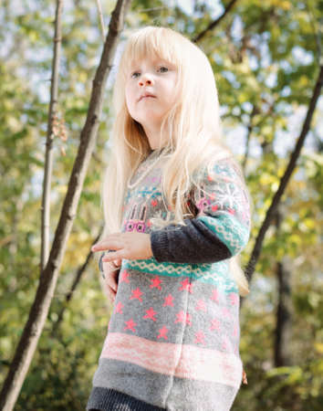 perturbed: Close up Pretty Little Girl, with Long Blond Hair, Wearing Autumn Fashion Outfit at the Woodland with Tall Trees Background.