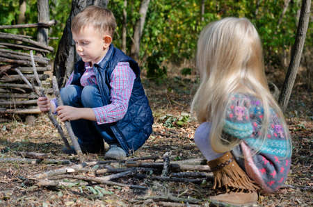 girl squatting: Two young children, a little boy and blond haired girl, squatting on the ground playing with sticks outdoors Stock Photo