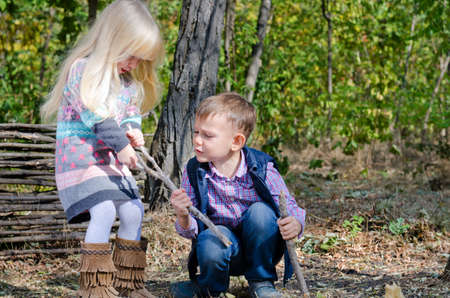 Two White Little Kids Fighting for Dried Stick while Playing at the Woods During Autumn Season.