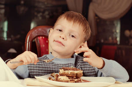 contented: Contented little boy eating a large slice of creamy cake for dessert as he sits smiling with pleasure at the dining table