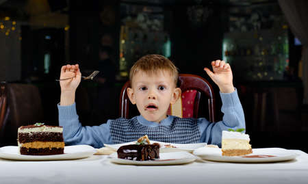 he is different: Cute young boy celebrating his birthday with a line up of different cake in front of him pulling a comic face as he tries to make up his mind where to begin eating