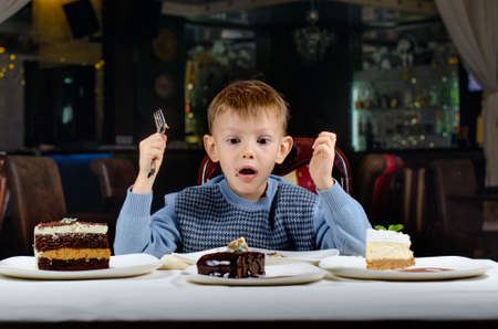 he is different: Little boy cannot believe his luck as he sits at the dining table holding a fork gawping at an array of different cakes spread out in front of him in wonderment