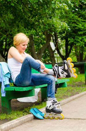 putting on: Attractive blond woman sitting on a park bench putting on roller blades as she prepares for a fun day skating
