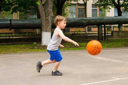 Kleine jongen spelen van basketbal lopen langs de rechter in zijn sportkleding stuiteren van de bal, zijaanzicht buitenshuis Stockfoto