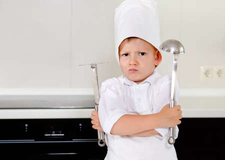 Cross determined little boy chef standing in his white apron and toque in the kitchen with his arms folded scowling at the camera