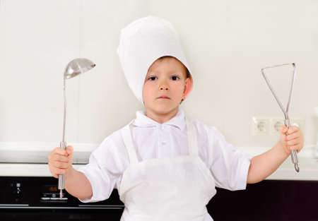 toque: Proud little boy chef in a white toque and apron holding up a stainless steel kitchen ladle and potato masher as he stands in the kitchen