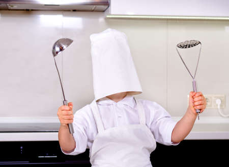 brandishing: Oops - my chefs hat is too big - a cute little boy in a white shirt and apron with his head inside a white toque stands in the kitchen holding stainless steel kitchen utensils