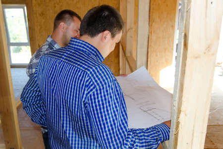 timber frame: Two carpenters or builders discussing a plan of the incomplete interior of a timber frame house during the construction process, over the shoulder view of the blueprint