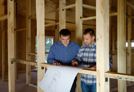 Two builders in a new build timber house standing discussing a blue print draped over a wooden beam
