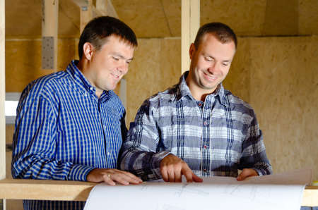 timber frame: Two builders discussing a building plan as they stand in the interior of a new build timber frame house still under construction