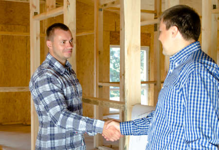 timber frame: Two middle-aged men standing shaking hands in a new build incomplete timber frame house interior in a conceptual image of ownership, partnership or two professionals allied to the building industry