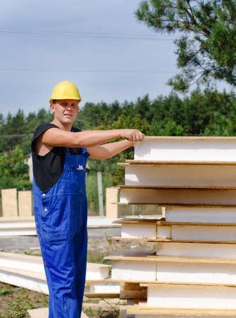 quizzical: Constructor de la selecci�n de un panel de pared de madera con aislamiento de una gran pila de suministros en la obra al aire libre que da a la c�mara una mirada seria burlona