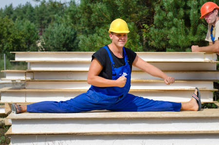 Funny fit worker wearing blue overalls and protection yellow hard hat while sitting in side split position on a pile of boards, during a break at work, outdoor, in a construction site, in summer