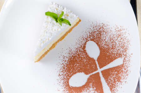 plating: Decorative plating and presentation of a slice of creamy cheesecake viewed from above with the outline of two crossed spoons in sprinkled cocoa powder alongside