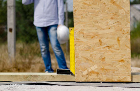perpendicular: Right angle in use on a building site ensuring that a wooden insulated wall panel is being installed in a perpendicular position Stock Photo