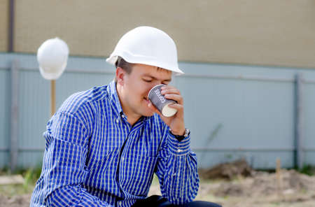 work workman: Close up side view of a young workman in a hardhat sipping coffee on a building site while the team continue work in the background