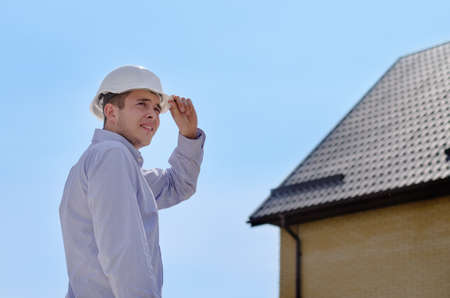 new build: Engineer, architect or building inspector standing in his hardhat checking a roof on a new build house against a blue sky