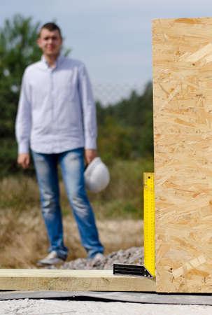 perpendicular: Angolo retto in uso su un cantiere garantire che un pannello parete in legno coibentato viene installato in posizione perpendicolare con un operaio piedi guardando in background