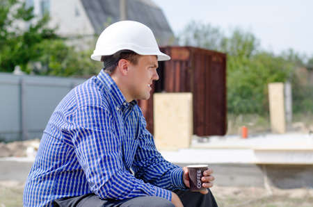 Foreman taking a coffee break on a building site sitting keeping an eye on his workmen as he relaxes over a mug of hot coffee, close up side view photo