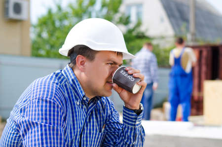 Young builder, engineer or architect taking his coffee break sipping from a plastic mug as his team continue working on site in the background Stock Photo