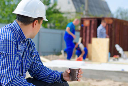 building site: Architect or engineer enjoying his coffee break sitting keeping an eye on his workmen, close up view from behind as he turns his head to watch