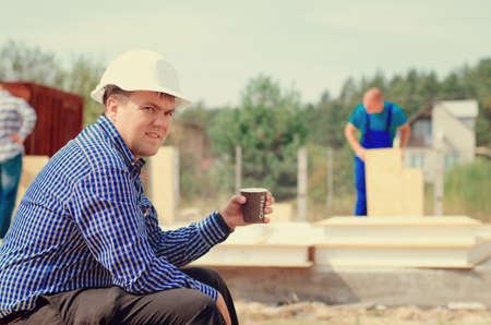 erecting: Site foreman taking a coffee break as the workmen continue working behind him erecting wall panels, closeup side view turning towards the camera with a serious expression