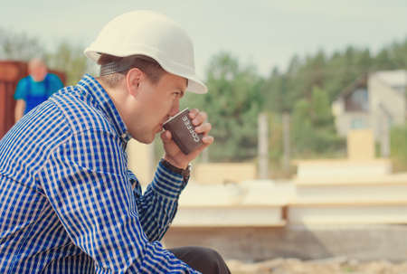 Architect taking a welcome coffee break sitting in his hardhat sipping coffee from a takeaway plastic mug on the building site, side view photo