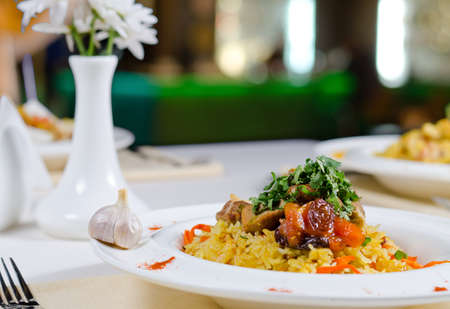 plating: Portions of roast meat on a bed on savory rice with carrots and fresh herbs served at a table in a restaurant, low angle close up view Stock Photo