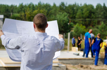 View from behind of a young architect or engineer checking a building plan on site holding it open in his hands as workmen work in the background photo