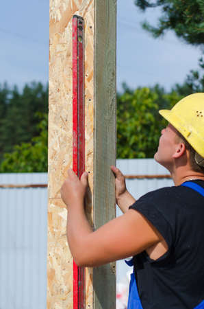 aligning: Builder ensuring that a beam is vertical holding a builders level against the wooden panel as he installs it on a new building during construction Stock Photo