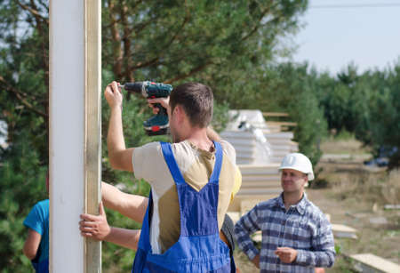 architect tools: Team of builders installing insulated wall panels on a residential building site watched by the architect, engineer, or foreman