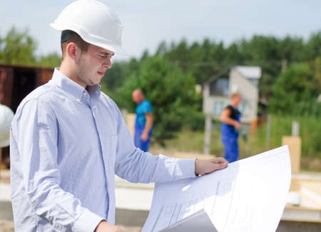 structural engineers: Architect or engineer checking plans on site holding the open blueprint in his hands as builders work in the background Stock Photo
