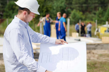 Architect or engineer checking plans on site holding the open blueprint in his hands as builders work in the background Standard-Bild