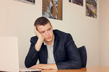 inscrutable: Young Businessman with Laptop in Office Resting Head on Hand and Looking Bored Stock Photo
