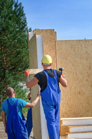 build in: Two builders installing an insulated wooden wall panel on a construction site for a new build house working outdoors in the sunshine
