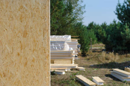 insulated: View past an erected installed panel on a residential building site of stacked wooden wall panels and scattered building supplies