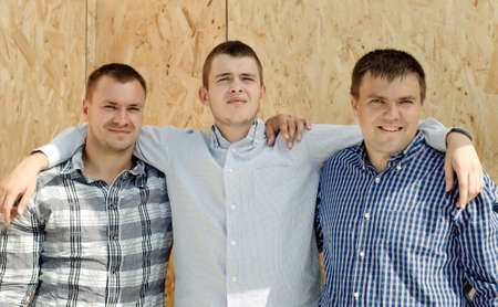 camaraderie: Three male friends standing arm in arm in front of a wooden wall panel smiling happily at the camera as they enjoy the camaraderie of being together