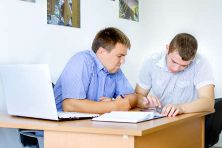 short sleeved: Young business team at work with two men in their short sleeved shirts sitting working on paperwork and a laptop at a desk in the office Stock Photo