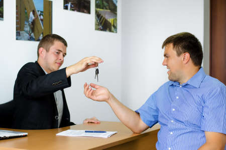 Stylish young salesman or agent handing keys to a client as they finalize a deal or the purchase of a property or car Standard-Bild