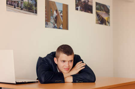 sombre: Young Businessman Resting Head on Desk and Looking Optimistic Stock Photo