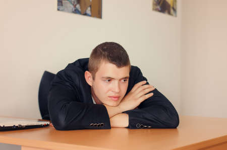unmotivated: Young Businessman Resting Head on Desk and Looking Optimistic Stock Photo