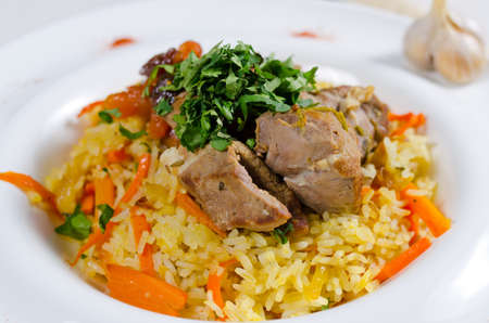 Savory saffron rice with bite size portions of roast meat, salad greens and vegetables served on a white plate for dinner Standard-Bild