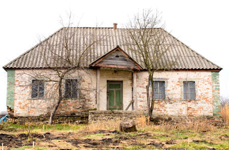 bleak: Exterior of Old Abandoned and Weathered Single Storey House with Bare Trees in Front Stock Photo