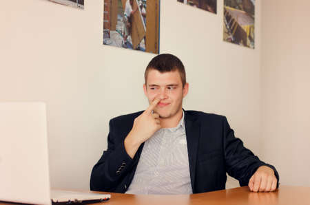 nose picking: Young Businessman Sitting at Desk Picking Nose in Office