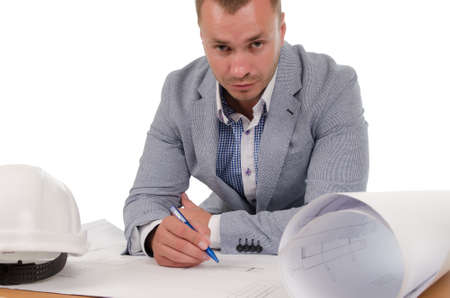 Architect or engineer sitting at a low table studying building plans with his hardhat alongside as he works on site