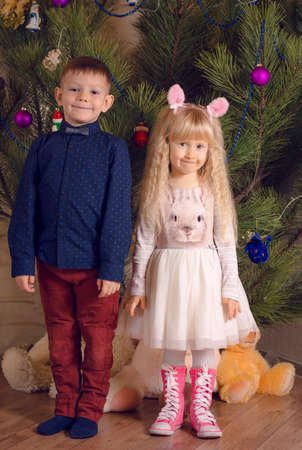 huge christmas tree: Full Length Shot of White Kids Posing in Front a Huge Christmas Tree While Looking at the Camera.