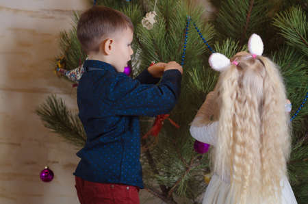huge christmas tree: Close up Young Boy and Girl Busy Decorating a Huge Christmas Tree at Home. Stock Photo