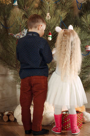 huge christmas tree: Close up Rear View of Kids, in Trendy Attire, Decorating a Huge Christmas Tree.